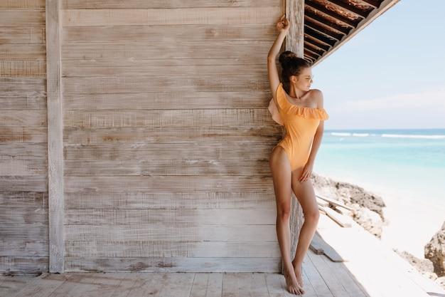 Knappe jonge vrouw draagt retro gele zwembroek poseren in de buurt van houten muur. buiten full-length portret van mooi gelooid meisje weekend ochtend doorbrengen in de buurt van zee. Gratis Foto