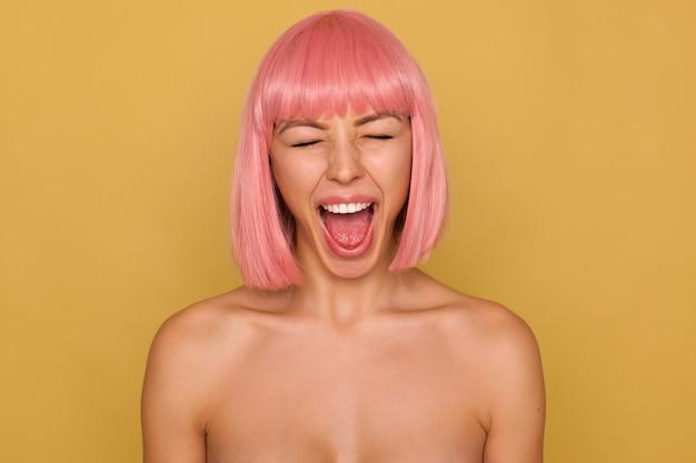 Knappe jonge vrouw met kort roze haar die haar mond wijd open houdt terwijl ze luid schreeuwt met gesloten ogen, geïsoleerd over mosterdmuur Gratis Foto
