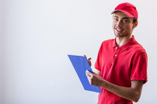 Knappe jonge werknemer in rode t-shirt en pet glimlachen. Premium Foto