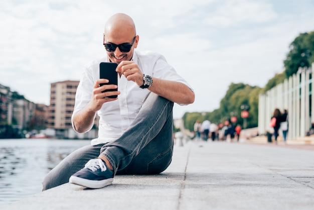 Knappe jonge zakenman in een wit overhemd gezeten door het water met behulp van smartphone Premium Foto