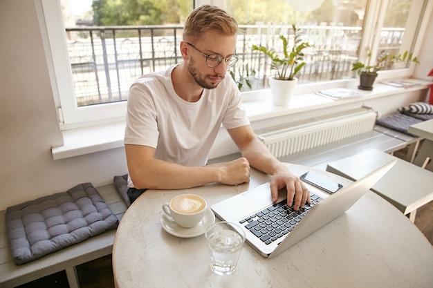 Knappe jonge zakenman zittend in een café met kopje koffie en laptop, bril en vrijetijdskleding, geconcentreerd en attent Gratis Foto