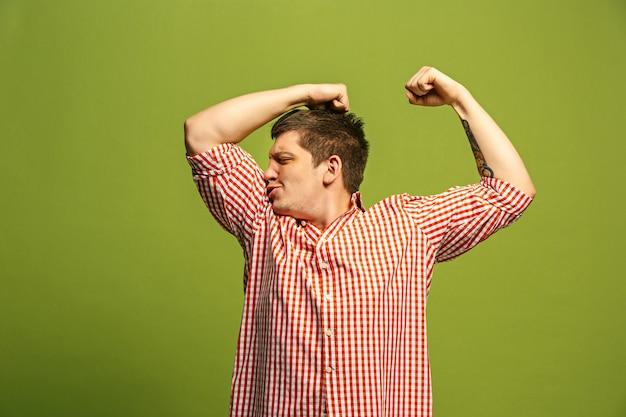 Knappe jongeman biceps tonen kracht en sportschool concept, gezond leven zijn goed uitdrukken. jonge emotionele verrast man die in de studio Gratis Foto