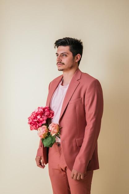 Knappe jongeman met bloemen in zijn broek, gekleed in een roze pak Premium Foto