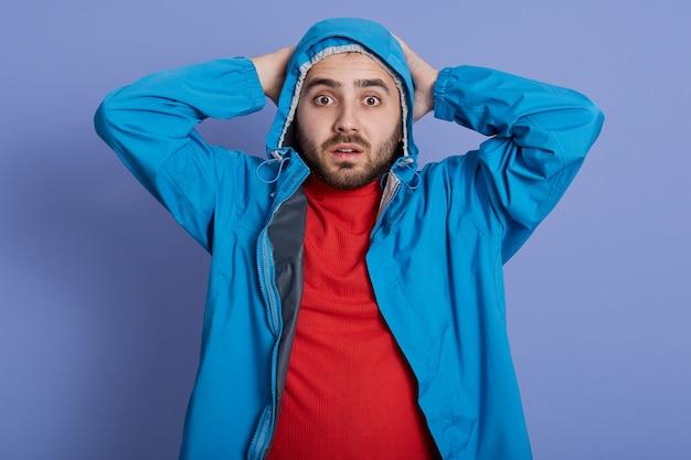 Knappe jongeman met het dragen van een blauwe jas en een rood shirt staan en zijn hoofd aan te raken, kijkend rechtstreeks naar de camera met grote ogen Gratis Foto