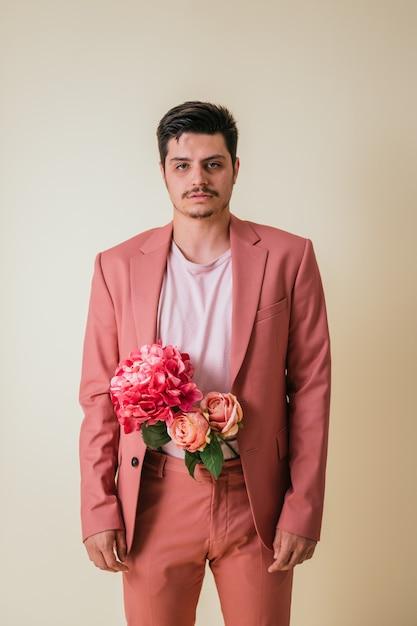 Knappe jongeman op zoek met bloemen in zijn broek, gekleed in een roze pak Premium Foto