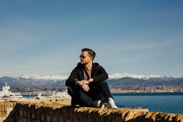 Knappe jongen zit op steen en kijkt naar schepen in het water van de zee. Premium Foto