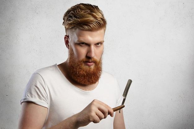 Knappe kapper met dikke baard die zijn kappersaccessoire vasthoudt en een scherp mes van een scheermes demonstreert. Gratis Foto