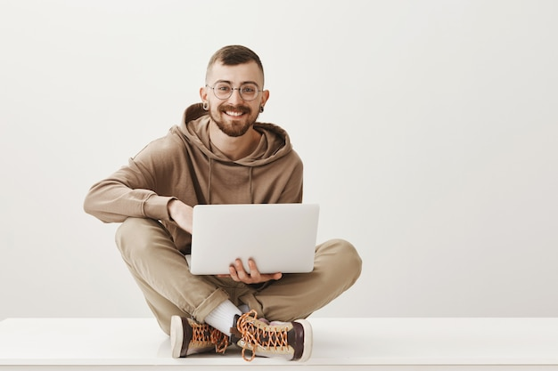 Knappe lachende man zit gekruiste benen en werkt via laptop Gratis Foto