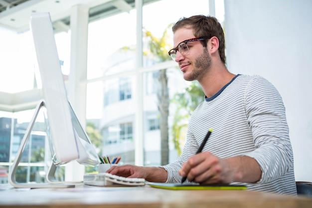 Knappe man aan het werk op computer in een heldere kantoor Premium Foto