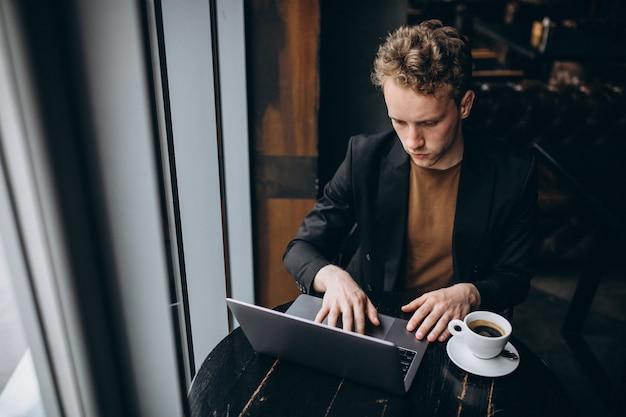 Knappe man aan het werk op een computer in een café en koffie drinken Gratis Foto