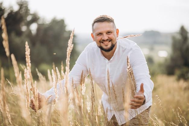 Knappe man buiten in een gouden veld Gratis Foto