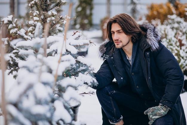 Knappe man die een kerstboom kiest Gratis Foto