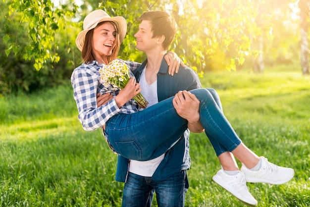Knappe man die gelukkige vrouw op handen Gratis Foto