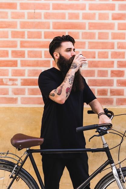 Knappe man die in de buurt van zijn cyclus tegen muur Gratis Foto