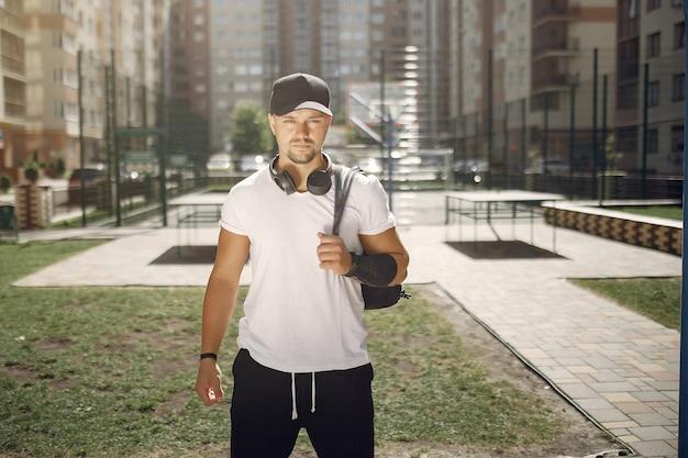 Knappe man die in een park met een koptelefoon Gratis Foto