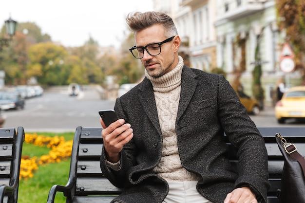 Knappe man draagt een jas zittend op een bankje buitenshuis, met behulp van mobiele telefoon Premium Foto
