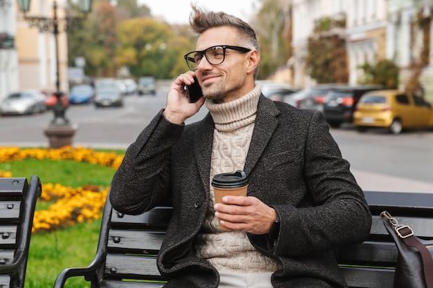 Knappe man draagt een jas zittend op een bankje buitenshuis, praten op mobiele telefoon, afhaalmaaltijden koffiekopje te houden Premium Foto