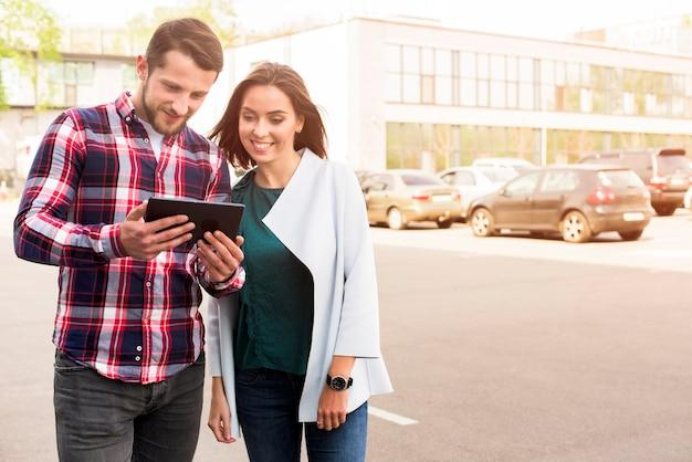 Knappe man en mooie vrouw kijken naar digitale tablet staande op straat Gratis Foto