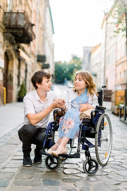 Knappe man en vrouw in rolstoel kijken elkaar op straat. mooi paar in een stoel die samen in de stad loopt Premium Foto
