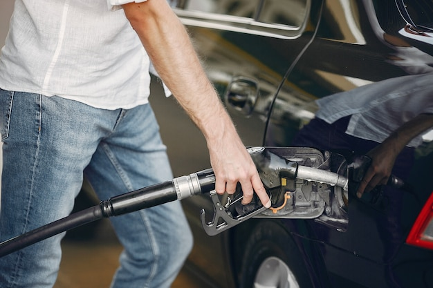 Knappe man giet benzine in de tank van de auto Gratis Foto