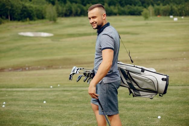 Knappe man golfen op een golfbaan Gratis Foto