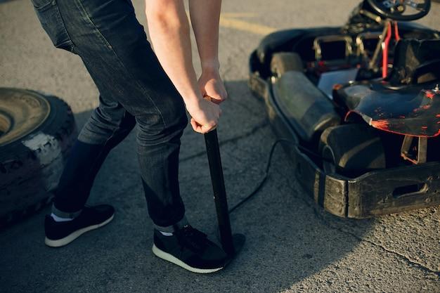 Knappe man in een karting met een auto Gratis Foto