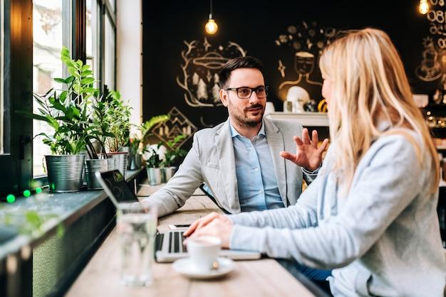 Knappe man in gesprek met een jonge blonde vrouw in het café. Premium Foto