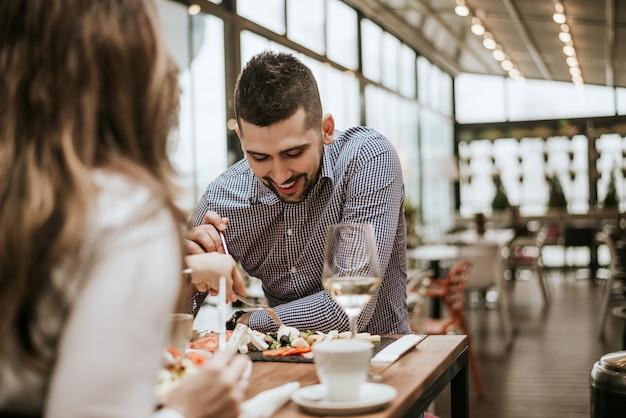 Knappe man in het restaurant met een vriend eten. Premium Foto