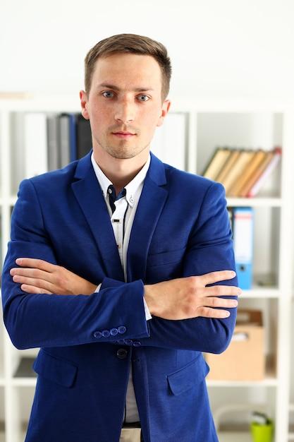 Knappe man in pak staan in kantoor Premium Foto