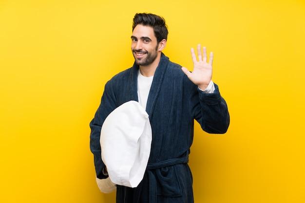 Knappe man in pyjama die met hand met gelukkige uitdrukking groeten Premium Foto