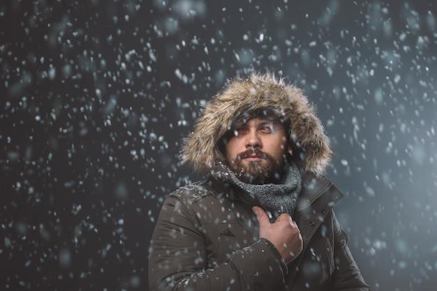 Knappe man in sneeuwstorm Gratis Foto