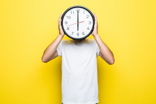 Knappe man in wit t-shirt en doorzichtige bril houdt grote klok in plaats van zijn hoofd Gratis Foto