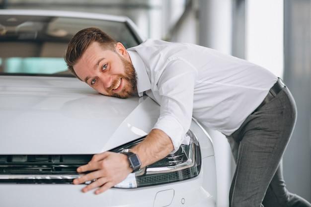 Knappe man knuffelen een auto in een showroom Gratis Foto