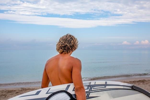 Knappe man lopen met witte lege surfplank wachten op golf om ter plaatse te surfen op zee oceaan kust Premium Foto