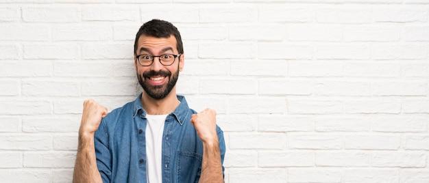 Knappe man met baard over witte bakstenen muur die een overwinning in winnaarpositie viert Premium Foto