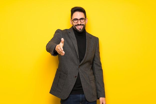Knappe man met bril handen schudden voor het sluiten van een goede deal Premium Foto