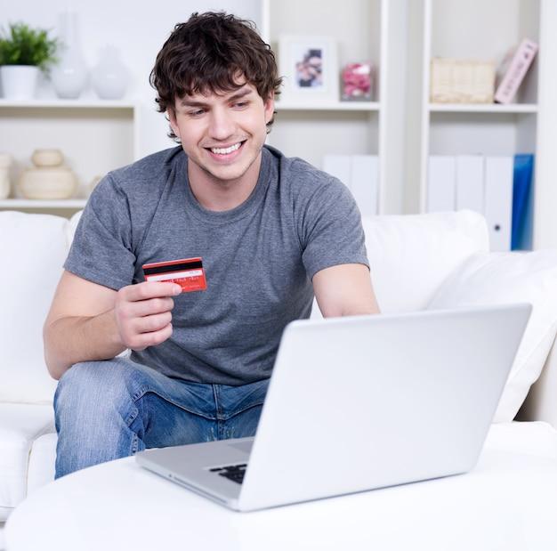 Knappe man met creditcard en laptop gebruikt voor online winkelen - binnenshuis Gratis Foto
