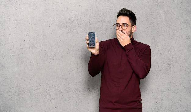 Knappe man met een bril met verontruste houden van gebroken smartphone over getextureerde muur Premium Foto