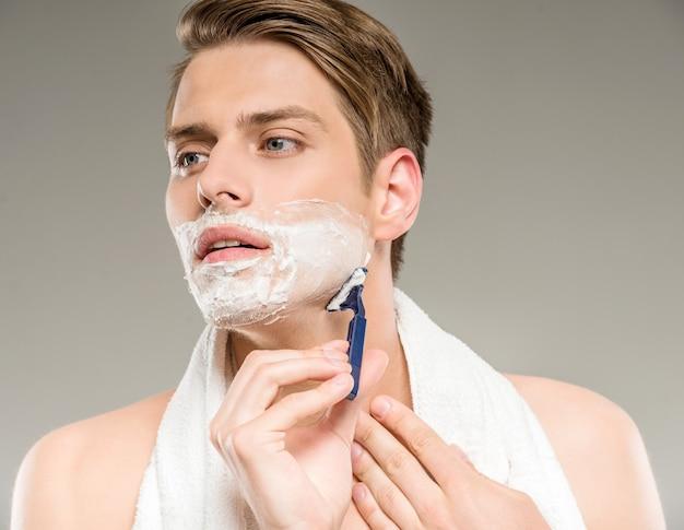 Knappe man met handdoek op schouders scheren na bad. Premium Foto