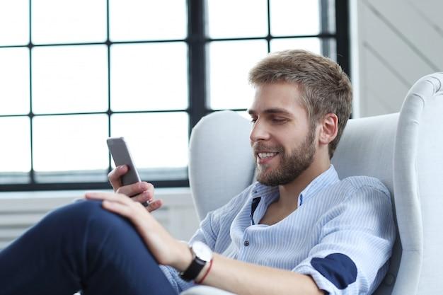 Knappe man met smartphone Gratis Foto