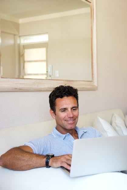 Knappe man om thuis te zitten met laptop Premium Foto