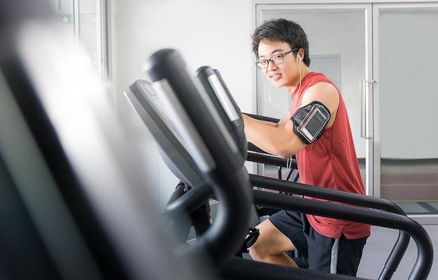 Knappe man op het runnen van machine in de sportschool, fitnessruimte Premium Foto