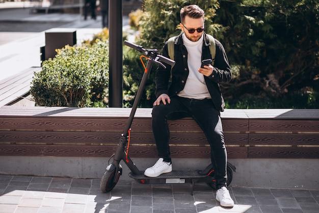Knappe man op scooter online winkelen op de telefoon Gratis Foto