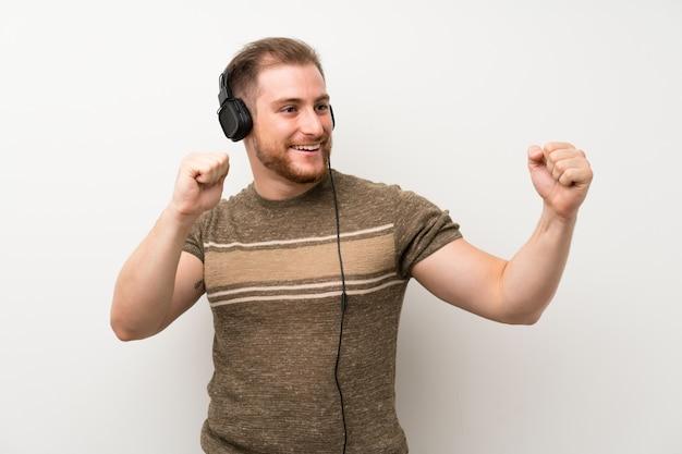 Knappe man over geïsoleerde witte muur luisteren naar muziek met een koptelefoon Premium Foto