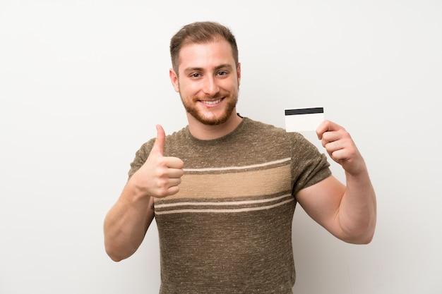 Knappe man over geïsoleerde witte muur met een creditcard Premium Foto