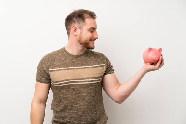 Knappe man over geïsoleerde witte muur met een grote spaarpot Premium Foto