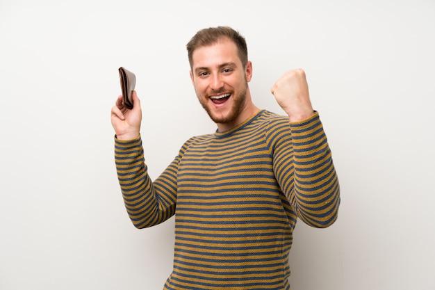 Knappe man over geïsoleerde witte muur met een portemonnee Premium Foto