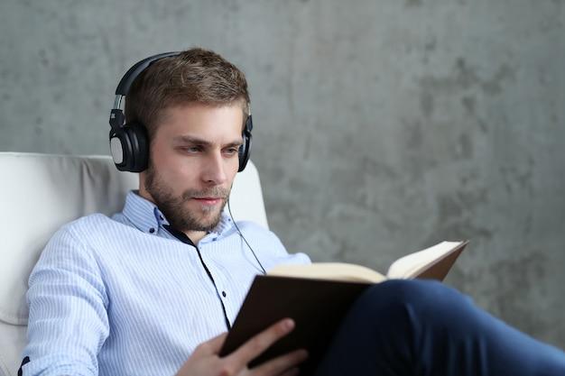 Knappe man podcast op koptelefoon luisteren Gratis Foto