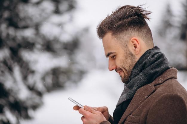 Knappe man praten aan de telefoon in een winter park Gratis Foto
