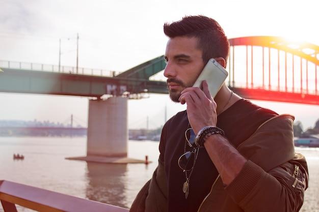 Knappe man praten buitenshuis aan de telefoon. met jas, zonnebril, een man met baard. instagram effect Gratis Foto
